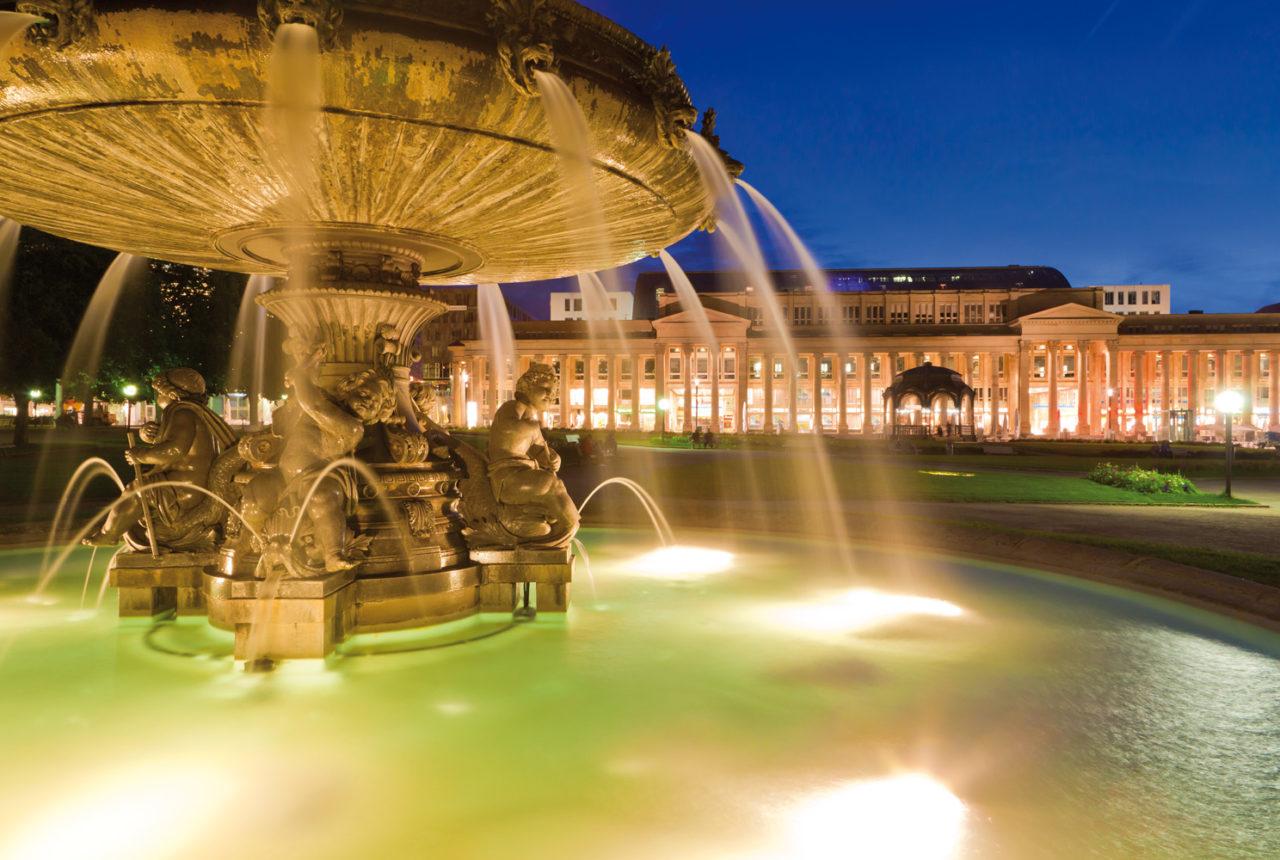 Beleuchteter Brunnen auf dem Stuttgarter Schlossplatz am Abend