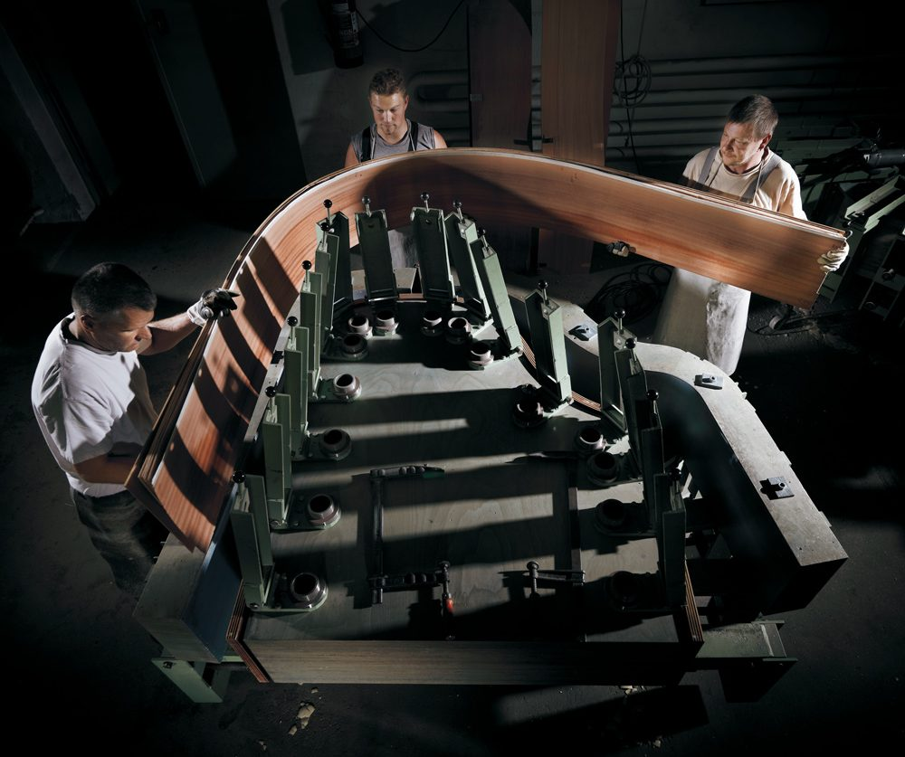 Bestein-Mitarbeiter spannen das Holz in den Rimbock, um es in Form zu biegen