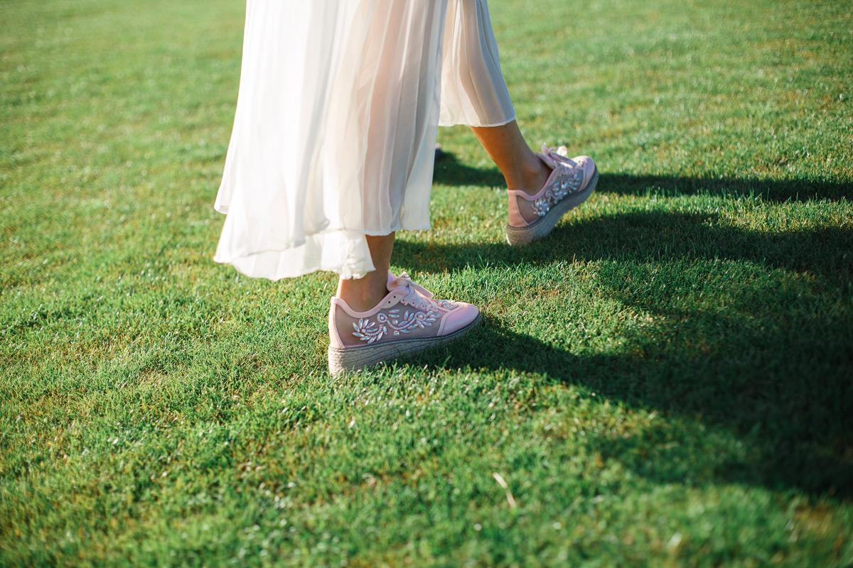 Frau mit Sommerkleid und Schuhen auf der Wiese