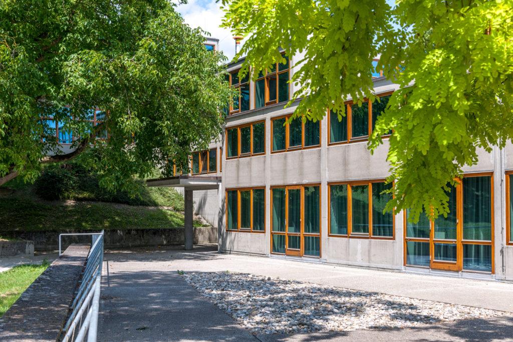 Die betongrauen Konstruktionsglieder, die den Rhythmus und die Struktur von Fassaden und Räumen ergeben, sind an der Außenfassade der HfG Ulm klar ablesbar